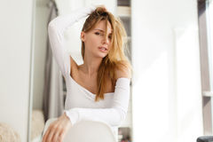 Beautiful girl on white chair. Beautiful girl sits on white chair in room Stock Images