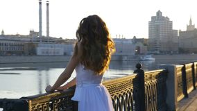 A beautiful girl in white clothes meets the dawn on the city embankment. Early morning, beautiful day. stock video
