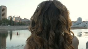 A beautiful girl in white clothes meets the dawn on the city embankment. Early morning, beautiful day.