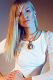 Beautiful girl in white dress and gold necklace with long blond straight hair. Stylish fashion photo of sexy beautiful slim model wearing a white dress and gold Royalty Free Stock Photography