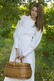 Beautiful girl in white dress holding a basket Stock Photos