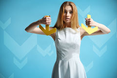 Beautiful girl in a white dress holding two arrows Royalty Free Stock Photo