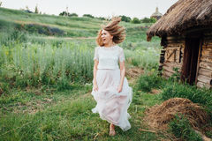 Beautiful girl in white dress lies in green grass Stock Image