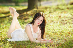 Beautiful girl in white dress lying on the grass Stock Photo