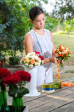 Beautiful girl in white dress making bouquets of roses in summer Stock Photography