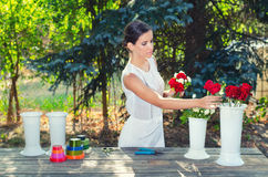 Beautiful girl in white dress making bouquets of roses Stock Photography