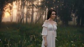 Beautiful girl in white dress posing on camera. stock footage