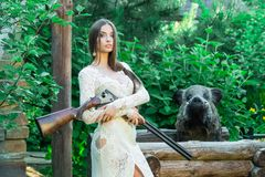 Beautiful girl in white dress posing with a hunting rifle and stuffed boar on background stock images