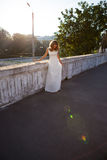 Beautiful girl in a white dress in the rays and glare of the sun Royalty Free Stock Photo