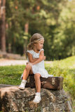 Beautiful girl in a white dress with retro hairstyle in the park Stock Image