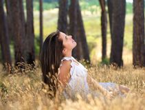 Beautiful girl in white dress sitting outdoors in a meadow Stock Photography