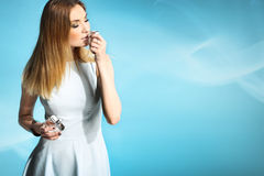 Beautiful girl in a white dress smelling perfume Royalty Free Stock Photos