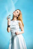 Beautiful girl in a white dress smelling perfume Stock Images