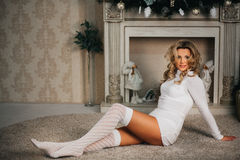 Beautiful girl  in a white dress and socks. Very beautiful blonde girl in a white dress and socks sitting on the background of the fireplace Royalty Free Stock Photos