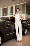 Beautiful girl in a white dress standing next to a car Royalty Free Stock Photo