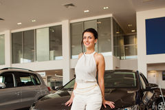 Beautiful girl in a white dress standing next to a car Stock Images
