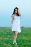 Beautiful girl in white dress walking on spring meadow Royalty Free Stock Photos