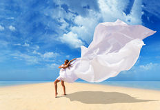 Beautiful Girl With White fabric on The Beach. Royalty Free Stock Photography