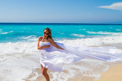 Beautiful Girl With White fabric on The Beach. Stock Photo