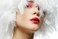 Beautiful Girl in white feathers. young woman royalty free stock photo