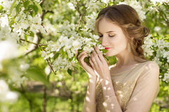 The beautiful girl and white flowers of the blossoming apple-tre. The beautiful wedding style girl among foliage and white flowers of the blossoming apple-trees Royalty Free Stock Photos