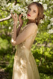 The beautiful girl and white flowers of the blossoming apple-tre. The beautiful wedding style girl among foliage and white flowers of the blossoming apple-trees Royalty Free Stock Image