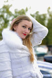 The beautiful girl in a white fur coat Stock Images
