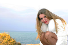 The beautiful girl in a white fur coat Stock Image