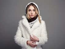 Beautiful girl in white fur coat and hood. winter fashion Royalty Free Stock Photography