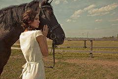 Beautiful girl in a white gown with horse Stock Images