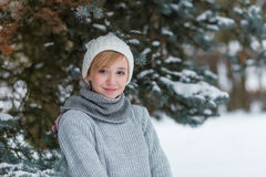 Beautiful girl in a white hat and mittens in the winter snowy fo Royalty Free Stock Images
