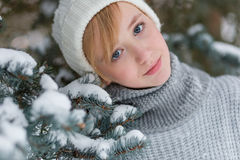 Beautiful girl in a white hat and mittens in the winter snowy fo Stock Images