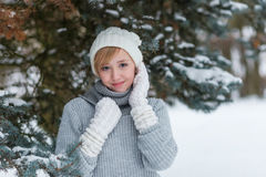 Beautiful girl in a white hat and mittens in the winter snowy fo Stock Image
