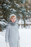 Beautiful girl in a white hat and mittens in the winter snowy fo Royalty Free Stock Image