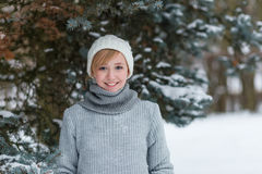 Beautiful girl in a white hat and mittens in the winter snowy fo Royalty Free Stock Photos