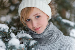 Beautiful girl in a white hat and mittens in the winter snowy fo Royalty Free Stock Photo