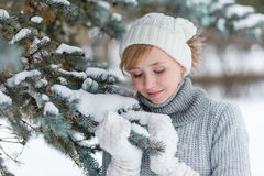 Beautiful girl in a white hat and mittens in the winter snowy fo Stock Photos