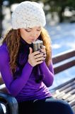 Beautiful girl in white hat sitting on a bench with a cup of coffee in the winter Royalty Free Stock Photography