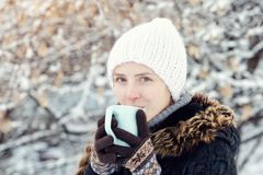 Beautiful girl in a white hat, wearing gloves and with a mug of Royalty Free Stock Images
