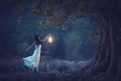 Beautiful girl in white holding a lantern in the autumn forest s. Hining under the trees royalty free stock photos