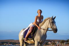 Beautiful girl on a white horse on background of the sea, in a dress of Amazon . Holiday and vacation concept