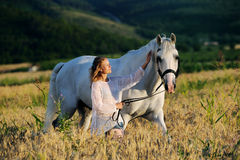 Beautiful girl with white horse in field Royalty Free Stock Photos