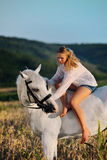 Beautiful girl with white horse in field Stock Photo