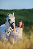 Beautiful girl with white horse in field. Beautiful girl with white horse in wheat field Royalty Free Stock Photography