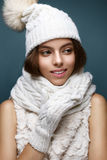 Beautiful girl in a white knitted hat with fur pompom. Model with gentle nude make-up. Cozy winter picture. Beautiful face Royalty Free Stock Image
