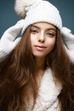 Beautiful girl in a white knitted hat with fur pompom. Model with gentle nude make-up. Cozy winter picture. Beautiful face Stock Photos