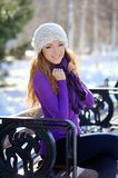 Beautiful girl in white knitted hat sitting on a bench in winter Royalty Free Stock Images