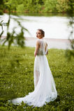 Beautiful girl in white long dress with open back. In full growth Stock Photos