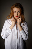 Beautiful girl in white men's shirt on dark background Stock Images