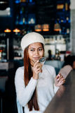 Beautiful girl in white outfit drinking Martini in a bar Royalty Free Stock Images